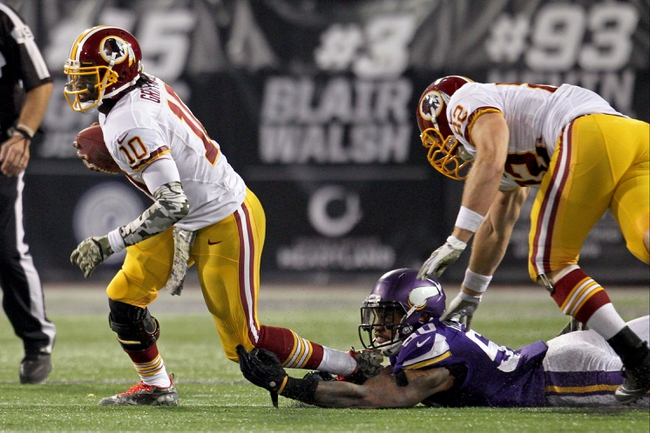 Nov 7, 2013; Minneapolis, MN, USA; Washington Redskins quarterback Robert Griffin III (10) escapes from Minnesota Vikings linebacker Erin Henderson (50) during the fourth quarter at Mall of America Field at H.H.H. Metrodome. The Vikings defeated the Redskins 34-27. Mandatory Credit: Brace Hemmelgarn-USA TODAY Sports
