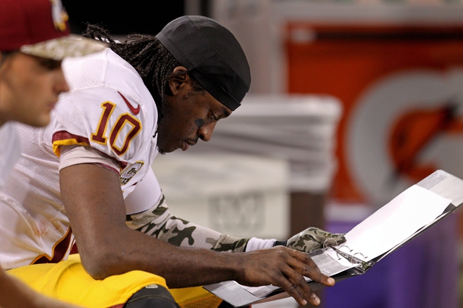 Nov 7, 2013; Minneapolis, MN, USA; Washington Redskins quarterback Robert Griffin III (10) looks at plays on the bench during the fourth quarter against the Minnesota Vikings at Mall of America Field at H.H.H. Metrodome. The Vikings defeated the Redskins 34-27. Mandatory Credit: Brace Hemmelgarn-USA TODAY Sports
