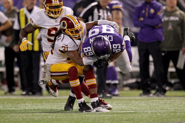 Nov 7, 2013; Minneapolis, MN, USA; Minnesota Vikings tight end John Carlson (89) is tackled by Washington Redskins safety Brandon Meriweather (31) during the fourth quarter at Mall of America Field at H.H.H. Metrodome. The Vikings defeated the Redskins 34-27. Mandatory Credit: Brace Hemmelgarn-USA TODAY Sports