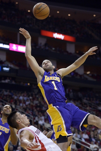 Nov 7, 2013; Houston, TX, USA; Houston Rockets point guard Jeremy Lin (7) draws a charge against Los Angeles Lakers point guard Jordan Farmar (1) during the second half at Toyota Center. The Lakers won 99-98. Mandatory Credit: Thomas Campbell-USA TODAY Sports