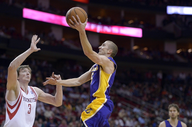 Nov 7, 2013; Houston, TX, USA; Los Angeles Lakers point guard Steve Blake (5) drives against Houston Rockets center Omer Asik (3) during the second half at Toyota Center. The Lakers won 99-98. Mandatory Credit: Thomas Campbell-USA TODAY Sports