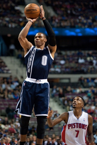 Nov 8, 2013; Auburn Hills, MI, USA; Detroit Pistons point guard Brandon Jennings (7) watches as Oklahoma City Thunder point guard Russell Westbrook (0) shoots during the first quarter at The Palace of Auburn Hills. Mandatory Credit: Tim Fuller-USA TODAY Sports