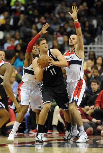 Nov 8, 2013; Washington, DC, USA; Brooklyn Nets center Brook Lopez (11) looks to pass as Washington Wizards shooting guard Bradley Beal (3) and center Marcin Gortat (4) defend during the first half at the Verizon Center. Mandatory Credit: Brad Mills-USA TODAY Sports