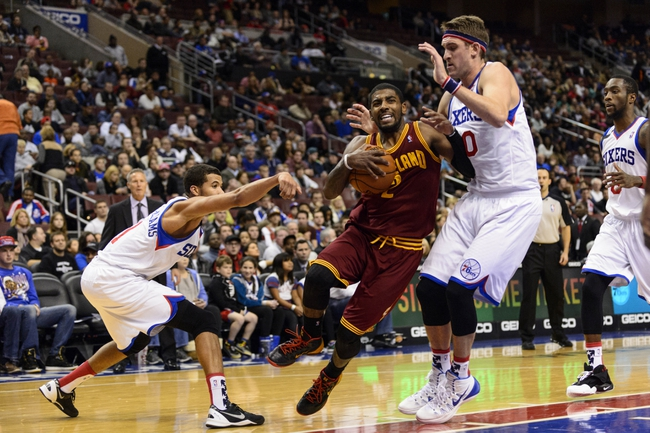 Nov 8, 2013; Philadelphia, PA, USA; Cleveland Cavaliers guard Kyrie Irving (2) drives to the basket while defended by Philadelphia 76ers guard Michael Carter-Williams (1) and center Spencer Hawes (00) during the fourth quarter at Wells Fargo Center. The Sixers defeated the Cavaliers 94-79. Mandatory Credit: Howard Smith-USA TODAY Sports