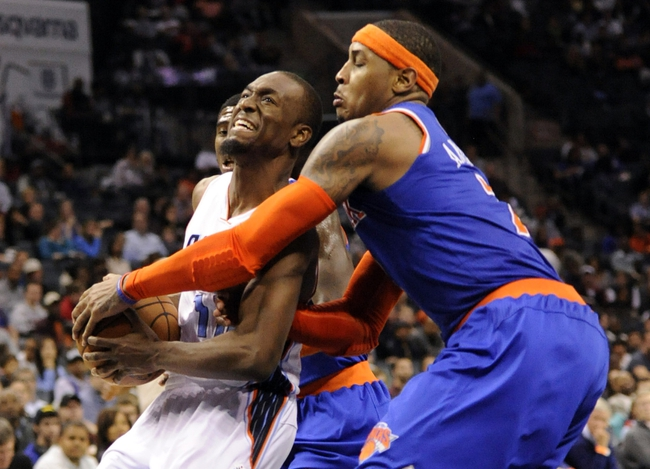 Nov 8, 2013; Charlotte, NC, USA; New York Knicks forward Carmelo Anthony (7) tries to stop Charlotte Bobcats guard Kemba Walker (15) as he drives to the basket and scores during the game at Time Warner Cable Arena. Knicks win 101-91. Mandatory Credit: Sam Sharpe-USA TODAY Sports