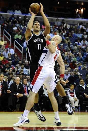 Nov 8, 2013; Washington, DC, USA; Brooklyn Nets center Brook Lopez (11) shoots over Washington Wizards center Marcin Gortat (4) during the second half at the Verizon Center. The Wizards defeated the Nets 112 - 108. Mandatory Credit: Brad Mills-USA TODAY Sports