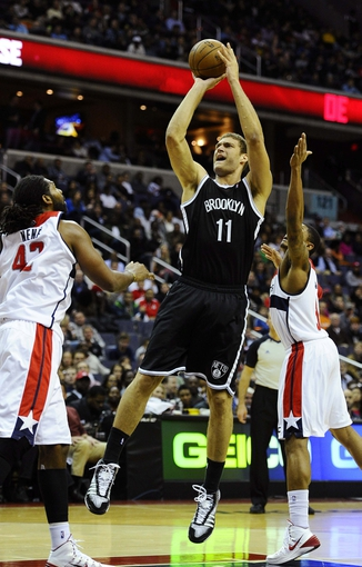 Nov 8, 2013; Washington, DC, USA; Brooklyn Nets center Brook Lopez (11) shoots over Washington Wizards power forward Nene Hilario (42) during the second half at the Verizon Center. The Wizards defeated the Nets 112 - 108. Mandatory Credit: Brad Mills-USA TODAY Sports