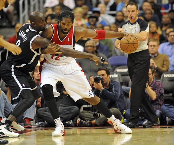 Nov 8, 2013; Washington, DC, USA; Washington Wizards power forward Nene Hilario (42) dribbles the ball as Brooklyn Nets power forward Kevin Garnett (2) defends during the second half at the Verizon Center. The Wizards defeated the Nets 112 - 108. Mandatory Credit: Brad Mills-USA TODAY Sports