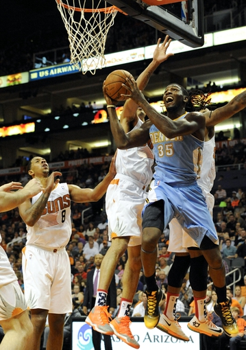 Nov 8, 2013; Phoenix, AZ, USA; Denver Nuggets small forward Kenneth Faried (35) shoots the ball as he is defended by Phoenix Suns power forward Channing Frye (8) and shooting guard Gerald Green (14) during the second quarter at US Airways Center. Mandatory Credit: Casey Sapio-USA TODAY Sports