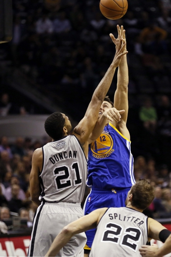 Nov 8, 2013; San Antonio, TX, USA; Golden State Warriors center Andrew Bogut (12) takes a shot over San Antonio Spurs forward Tim Duncan (21) during the second half at AT&T Center. The Spurs won 76-74. Mandatory Credit: Soobum Im-USA TODAY Sports