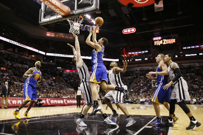 Nov 8, 2013; San Antonio, TX, USA; Golden State Warriors guard Klay Thompson (top) drives to the basket as San Antonio Spurs forward Aron Baynes (left) defends during the second half at AT&T Center. The Spurs won 76-74. Mandatory Credit: Soobum Im-USA TODAY Sports