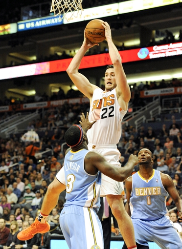 Nov 8, 2013; Phoenix, AZ, USA; Phoenix Suns power forward Miles Plumlee (22) shoots the ball over Denver Nuggets point guard Ty Lawson (3) during the third quarter at US Airways Center. The Suns defeated the Nuggets 114-103. Mandatory Credit: Casey Sapio-USA TODAY Sports