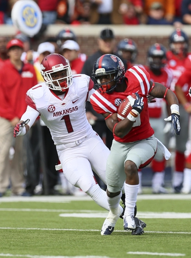 Nov 9, 2013; Oxford, MS, USA; Mississippi Rebels running back Jaylen Walton (6) advances the ball against Arkansas Razorbacks cornerback D.J. Dean (1) during the game at Vaught-Hemingway Stadium. Mandatory Credit: Spruce Derden-USA TODAY Sports