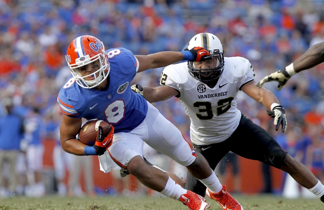 Nov 9, 2013; Gainesville, FL, USA; Florida Gators wide receiver Trey Burton (8) runs with the ball as Vanderbilt Commodores safety Andrew Williamson (32) defends during the second half at Ben Hill Griffin Stadium. Vanderbilt Commodores defeated the Florida Gators 34-17. Mandatory Credit: Kim Klement-USA TODAY Sports