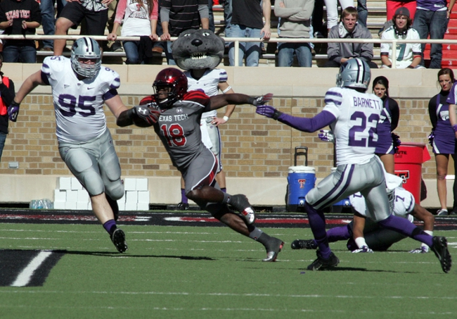 Nov 9, 2013; Lubbock, TX, USA; Texas Tech Red Raiders wide receiver Eric Ward (18) rushes between Kansas State Wildcats defensive tackle Travis Britz (95) and safety Dante Barnett (22) in the second half at Jones AT&T Stadium. Mandatory Credit: Michael C. Johnson-USA TODAY Sports