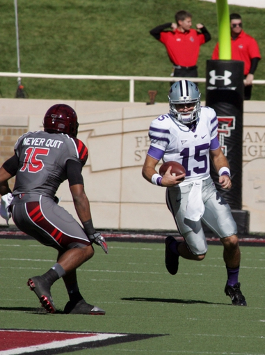 Nov 9, 2013; Lubbock, TX, USA; Kansas State Wildcats quarterback Jake Waters (15) rushes against Texas Tech Red Raiders free safety Keenon Ward (15) in the first half at Jones AT&T Stadium. Mandatory Credit: Michael C. Johnson-USA TODAY Sports