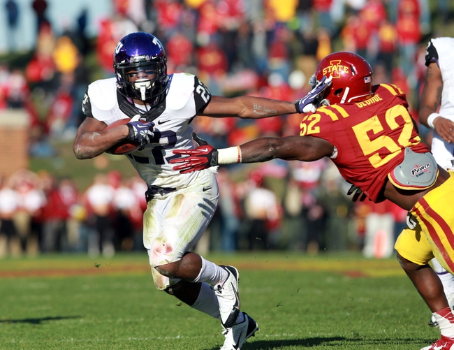 Nov 9, 2013; Ames, IA, USA; Texas Christian Horned Frogs running back Aaron Green (22) stiff arms Iowa State Cyclones linebacker Jeremiah George (52) at Jack Trice Stadium.  Texas Christian beat Iowa State 21-17.  Mandatory Credit: Reese Strickland-USA TODAY Sports