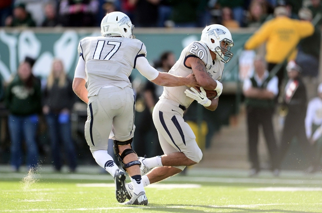 Nov 9, 2013; Fort Collins, CO, USA; Nevada Wolf Pack quarterback Cody Fajardo (17) hands off to running back Chris Solomon (20) in the second quarter against the Colorado State Rams at Hughes Stadium. Mandatory Credit: Ron Chenoy-USA TODAY Sports