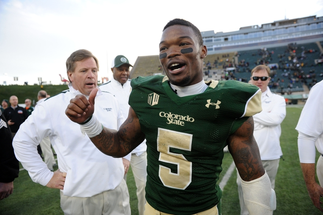 Nov 9, 2013; Fort Collins, CO, USA; Colorado State Rams running back Kapri Bibbs (5) reacts following the win over the Nevada Wolf Pack with head coach Jim McElwain at Hughes Stadium. The Rams defeated the Wolf Pack 38-17. Mandatory Credit: Ron Chenoy-USA TODAY Sports