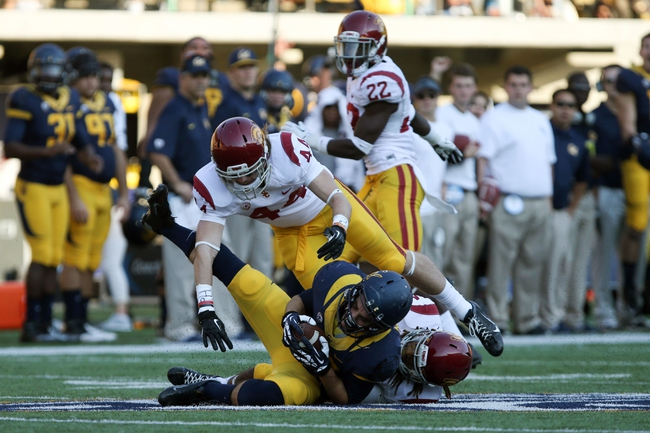 Nov 9, 2013; Berkeley, CA, USA; California Golden Bears wide receiver Bryce McGovern (86) catches the ball between USC Trojans safety Rob Dooley (44) and cornerback Ryan Henderson (14) during the fourth quarter at Memorial Stadium. The USC Trojans defeated the California Golden Bears 62-28. Mandatory Credit: Kelley L Cox-USA TODAY Sports