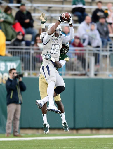 Nov 9, 2013; Fort Collins, CO, USA; Nevada Wolf Pack quarterback Dustin Treick (12) pulls in a reception as Colorado State Rams cornerback Shaq Bell (3) defends at in the fourth quarter Hughes Stadium. The Rams defeated the Wolf Pack 38-17.Mandatory Credit: Ron Chenoy-USA TODAY Sports