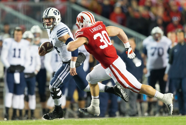 Nov 9, 2013; Madison, WI, USA; Brigham Young Cougars quarterback Taysom Hill (4) rushes with the football as Wisconsin Badgers linebacker Derek Landisch (30) chases from behind during the fourth quarter at Camp Randall Stadium. Wisconsin won 27-17.  Mandatory Credit: Jeff Hanisch-USA TODAY Sports