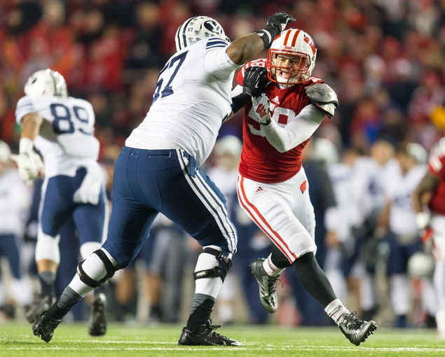 Nov 9, 2013; Madison, WI, USA; Wisconsin Badgers linebacker Joe Schobert (58) rushes as Brigham Young Cougars offensive lineman De'Ondre Wesley (57) blocks  during the fourth quarter at Camp Randall Stadium. Wisconsin won 27-17.  Mandatory Credit: Jeff Hanisch-USA TODAY Sports
