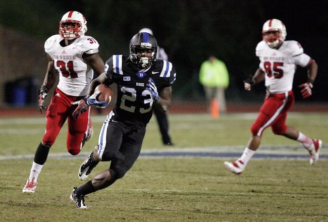 Nov 9, 2013; Durham, NC, USA; Duke Blue Devils running back Juwan Thompson (23) runs past North Carolina State Wolfpack linebacker D.J. Green (31) at Wallace Wade Stadium. Mandatory Credit: Mark Dolejs-USA TODAY Sports