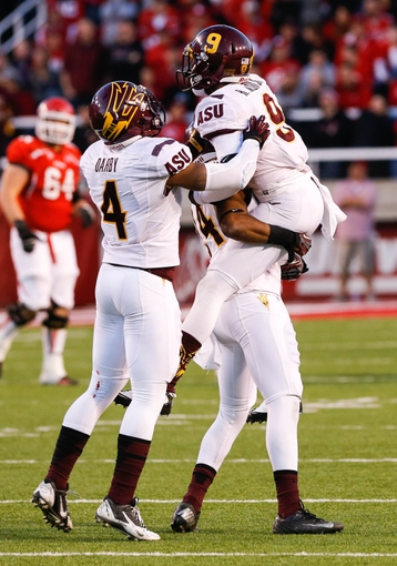 Nov 9, 2013; Salt Lake City, UT, USA; Arizona State Sun Devils defensive back Robert Nelson (9) is lifted up by cornerback Osahon Irabor (24) celebrating Nelson's interception during the fourth quarter in the game against the Utah Utes at Rice-Eccles Stadium. Arizona State Sun Devils won the game 20-19. Mandatory Credit: Chris Nicoll-USA TODAY Sports