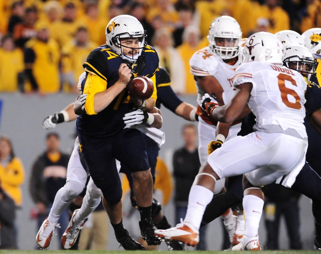 Nov 9, 2013; Morgantown, WV, USA; West Virginia Mountaineers quarterback Paul Millard (14) gets sacked and fumbles the ball in the second quarter against the Texas Longhorns at Milan Puskar Stadium. Mandatory Credit: Evan Habeeb-USA TODAY Sports