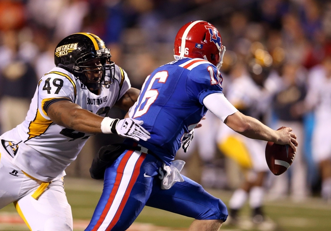 Nov 9, 2013; Ruston, LA, USA; Southern Miss Golden Eagles defensive lineman Adam Williams (49) pressures Louisiana Tech Bulldogs quarterback Scotty Young (16) during the second quarter at Joe Aillet Stadium. Mandatory Credit: Chuck Cook-USA TODAY Sports