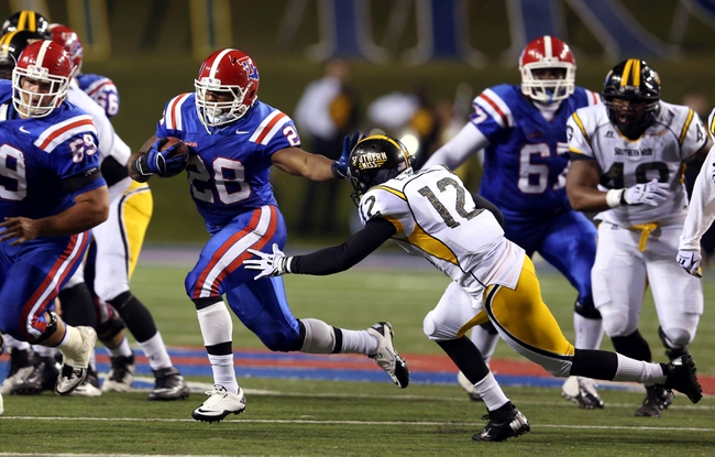 Nov 9, 2013; Ruston, LA, USA; Louisiana Tech Bulldogs running back Kenneth Dixon (28) runs past Southern Miss Golden Eagles defensive back Emmanuel Johnson (12) during the second quarter at Joe Aillet Stadium. Mandatory Credit: Chuck Cook-USA TODAY Sports