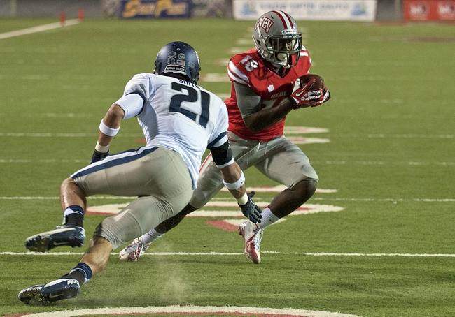 Nov 9, 2013; Las Vegas, NV, USA; UNLV Rebels wide receiver Marcus Sullivan (18) makes a cut to avoid Utah State Aggies safety Brian Suite (21) on his way to scoring a touchdown during an NCAA football game at Sam Boyd Stadium. Mandatory Credit: Stephen R. Sylvanie-USA TODAY Sports