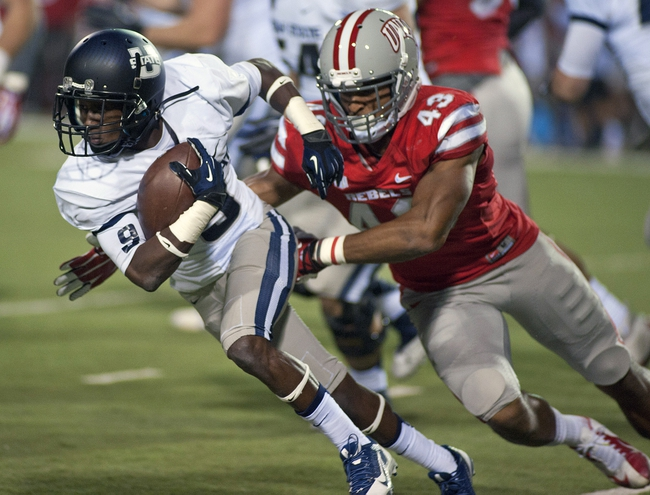 Nov 9, 2013; Las Vegas, NV, USA; Utah State Aggies wide receiver Bruce Natson (9) attempts to evade the tackle of UNLV Rebels line backer Tim Hasson (43) during an NCAA football game at Sam Boyd Stadium. Mandatory Credit: Stephen R. Sylvanie-USA TODAY Sports