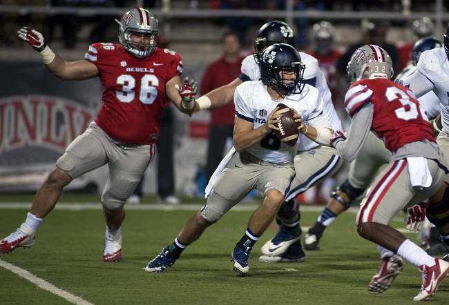 Nov 9, 2013; Las Vegas, NV, USA; [CAPTION] Utah State Aggies quarterback Darell Garretson (6) steps into a collapsing pocket as he seeks an open receiver during an NCAA football game against the UNLV Rebels at Sam Boyd Stadium. Mandatory Credit: Stephen R. Sylvanie-USA TODAY Sports