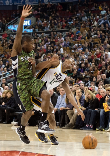 Nov 9, 2013; Toronto, Ontario, CAN; Utah Jazz point guard Alec Burks (10) is fouled by Toronto Raptors point guard Dwight Buycks (13) during the second period in a game at Air Canada Centre. 