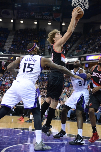 November 9, 2013; Sacramento, CA, USA; Portland Trail Blazers center Robin Lopez (42, top) shoots the ball against Sacramento Kings center DeMarcus Cousins (15) and power forward Patrick Patterson (9) during the first quarter at Sleep Train Arena. Mandatory Credit: Kyle Terada-USA TODAY Sports