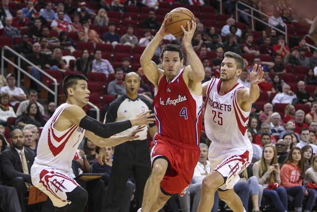 Nov 9, 2013; Houston, TX, USA; Los Angeles Clippers shooting guard J.J. Redick (4) drives the ball to the basket during the fourth quarter as Houston Rockets small forward Chandler Parsons (25) and point guard Jeremy Lin (7) defend at Toyota Center. The Clippers defeated the Rockets 107-94. Mandatory Credit: Troy Taormina-USA TODAY Sports