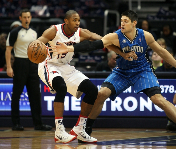 Nov 9, 2013; Atlanta, GA, USA; Atlanta Hawks center Al Horford (15) is defended by Orlando Magic center Nikola Vucevic (9) in the first half at Philips Arena. Mandatory Credit: Brett Davis-USA TODAY Sports
