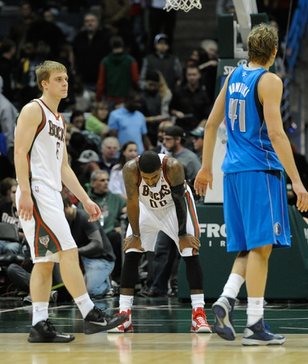Nov 9, 2013; Milwaukee, WI, USA; Milwaukee Bucks guard O.J. Mayo (center) reacts with guard Nate Wolters (left) and Dallas Mavericks forward Dirk Nowitzki (right) after the Mavericks beat the Bucks 91-83 at BMO Harris Bradley Center. Mandatory Credit: Benny Sieu-USA TODAY Sports