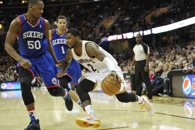 Nov 9, 2013; Cleveland, OH, USA; Cleveland Cavaliers point guard Kyrie Irving (2) dribbles past Philadelphia 76ers power forward Lavoy Allen (50) and point guard Michael Carter-Williams (1) in the fourth quarter at Quicken Loans Arena. Mandatory Credit: David Richard-USA TODAY Sports