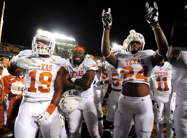 Nov 9, 2013; Morgantown, WV, USA; Texas Longhorns running back Joe Bergeron (24) cornerback Leroy Scott (31) and linebacker Peter Jinkens (19) celebrate after beating the West Virginia Mountaineers 47-40 in overtime at Milan Puskar Stadium. Mandatory Credit: Evan Habeeb-USA TODAY Sports