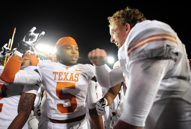 Nov 9, 2013; Morgantown, WV, USA; Texas Longhorns quarterback Case McCoy (right) celebrates with safety Josh Turner (left) after beating the West Virginia Mountaineers 47-40 in overtime at Milan Puskar Stadium. Mandatory Credit: Evan Habeeb-USA TODAY Sports