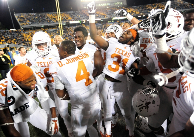 Nov 9, 2013; Morgantown, WV, USA; Texas Longhorns cornerback Leroy Scott (31) celebrates with teammates after beating the West Virginia Mountaineers 47-40 in overtime at Milan Puskar Stadium. Mandatory Credit: Evan Habeeb-USA TODAY Sports
