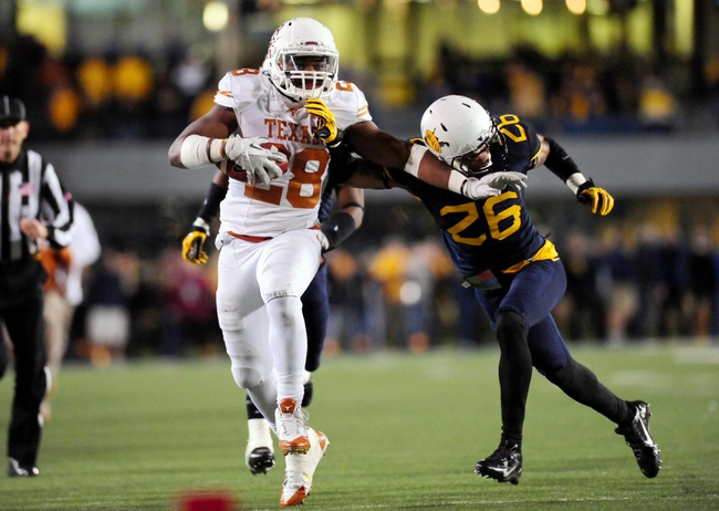 Nov 9, 2013; Morgantown, WV, USA; Texas Longhorns running back Malcolm Brown (28) gives a stiff arm to West Virginia Mountaineers cornerback Travis Bell (26) at Milan Puskar Stadium. Mandatory Credit: Evan Habeeb-USA TODAY Sports