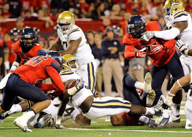 Nov 9, 2013; Tucson, AZ, USA; UCLA Bruins linebacker Myles Jack (30) gets tripped up during the second quarter against the Arizona Wildcats at Arizona Stadium. Mandatory Credit: Casey Sapio-USA TODAY Sports