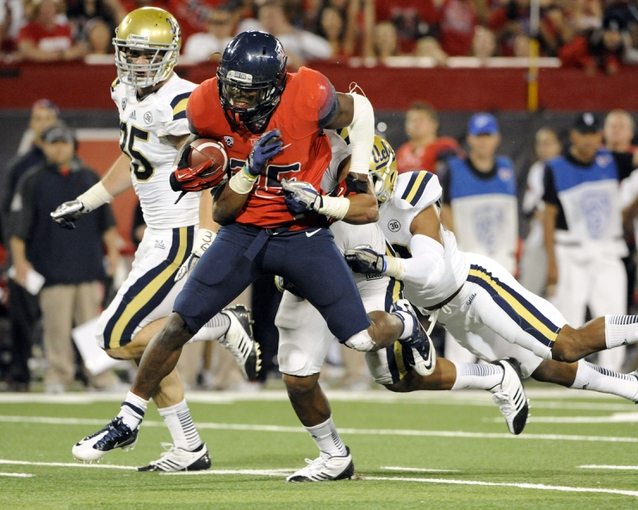 Nov 9, 2013; Tucson, AZ, USA; Arizona Wildcats running back Ka   Deem Carey (25) is tackled by UCLA Bruins inside linebacker Eric Kendricks (6) during the fourth quarter at Arizona Stadium. Mandatory Credit: Casey Sapio-USA TODAY Sports