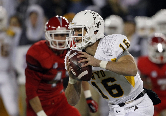 Nov 9, 2013; Laramie, WY, USA; Wyoming Cowboys quarterback Brett Smith (16) runs against the Fresno State Bulldogs during the second quarter at War Memorial Stadium. The Bulldogs defeated the Cowboys 48-10. Mandatory Credit: Troy Babbitt-USA TODAY Sports