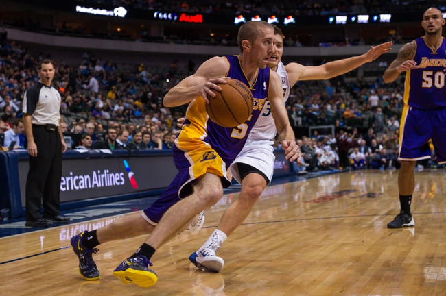 Nov 5, 2013; Dallas, TX, USA; Los Angeles Lakers point guard Steve Blake (5) drives to the basket past Dallas Mavericks point guard Gal Mekel (33) during the game at the American Airlines Center. The Mavericks defeated the Lakers 123-104.  Mandatory Credit: Jerome Miron-USA TODAY Sports