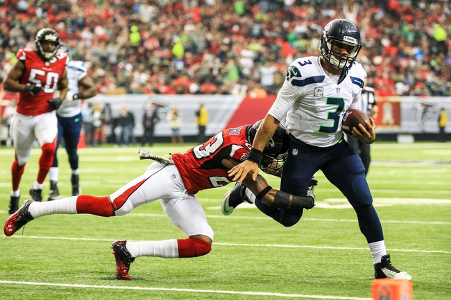 Nov 10, 2013; Atlanta, GA, USA; Seattle Seahawks quarterback Russell Wilson (3) stiff arms Atlanta Falcons safety Thomas DeCoud (28) on a run in the first half at the Georgia Dome. Mandatory Credit: Daniel Shirey-USA TODAY Sports